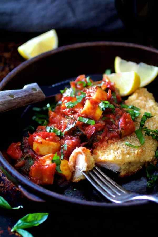 Chicken Scallopini with Roasted Vegetable Ratatouille - Close-up hero shot in clay dish garnished with lemon wedges with a piece on a fork