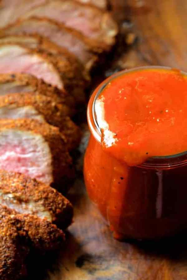Spice Rubbed Pork Tenderloin with Peach Chipotle Barbecue Sauce - Close-up shot of sauce in glass jar with sliced pork tenderloin off to the side