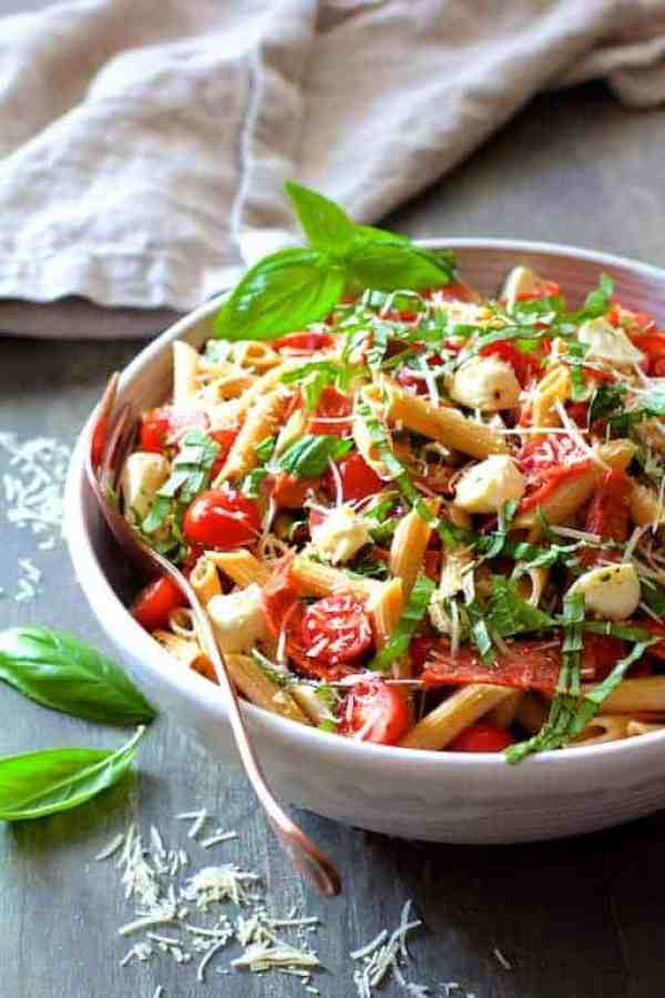 Caprese Pizza Pasta Salad - Hero shot of salad in white bowl on gray background with Parmesan cheese and fresh basil leaves scattered around and gray napkin the background