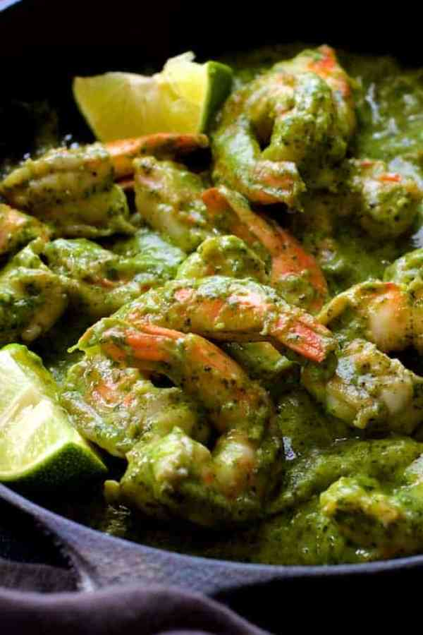 Shrimp in Avocado Butter - Close-up shot of the dish in the cast iron skillet garnished with lime wedges