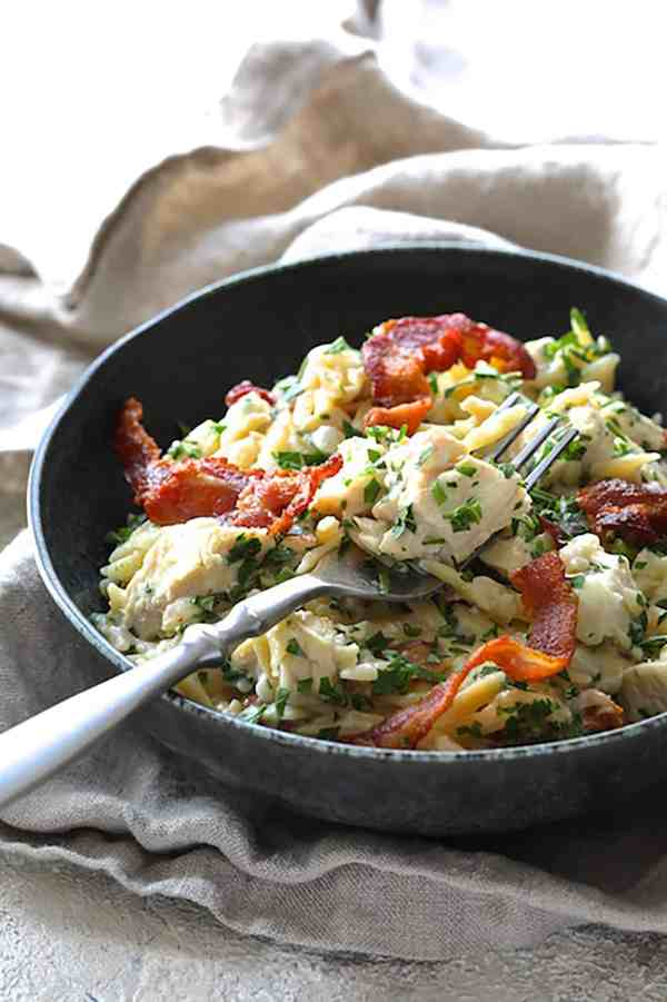 Creamy One Pot Chicken and Orzo Risotto with Bacon - Straight-on shot of dish in black bowl with chicken on fork ready to be eaten