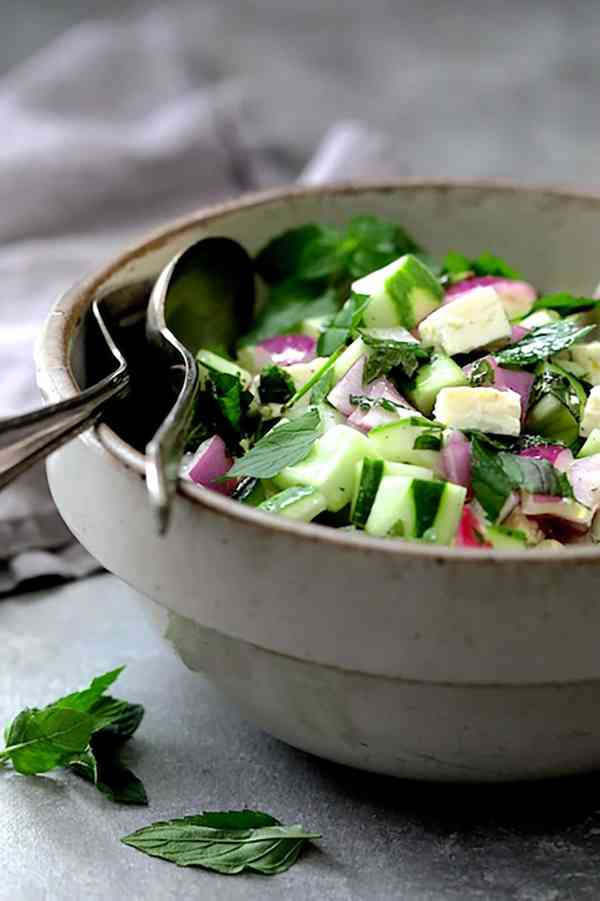 Cucumber Red Onion Salad Feta Cheese - Close-up straight-on shot of salad in stoneware bowl with serving utensils