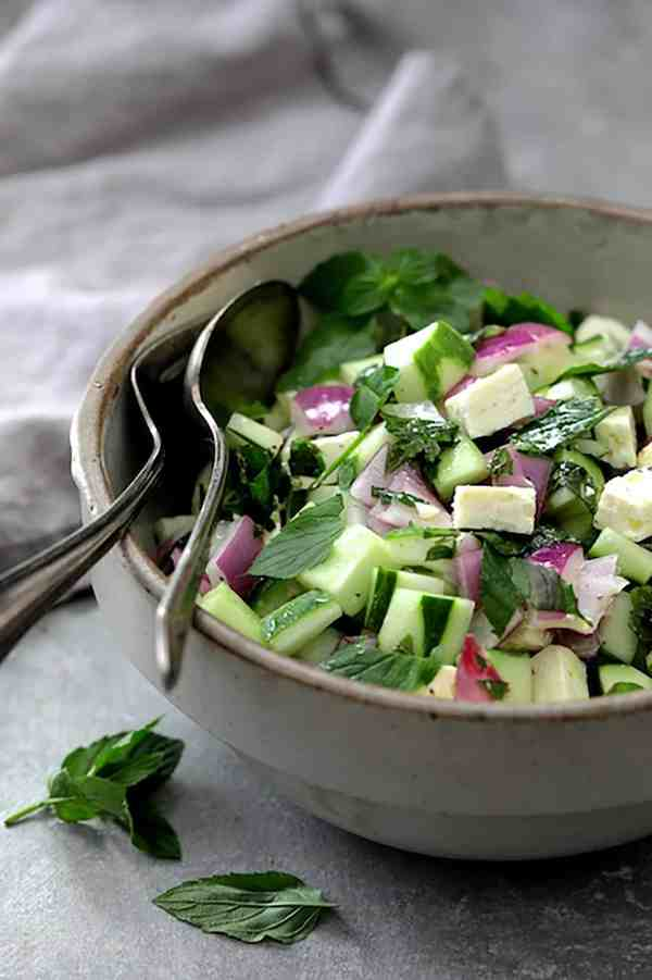 Cucumber Red Onion Salad Feta Cheese - Photo of salad in stoneware bowl with gray napkin on gray background