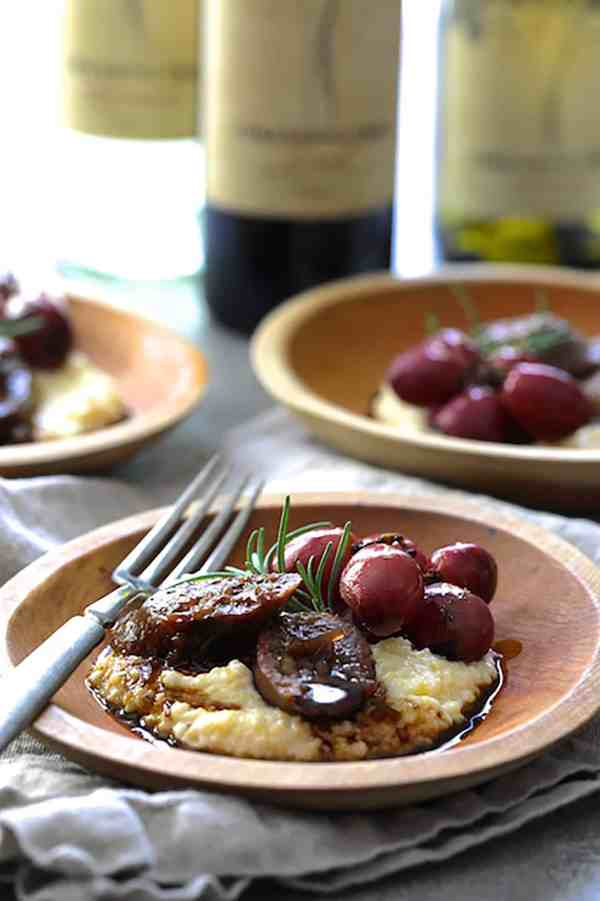 Balsamic Italian Sausage and Grapes over Goat Cheese Polenta - Close-up straight-on shot of dish in small wooden bowl with wine bottles in the background