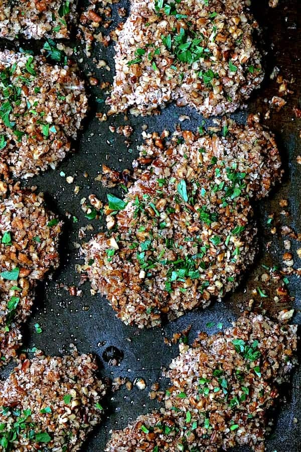 Pecan Crusted Turkey Cutlets with Red Onion Marmalade - Top Down Shot of Pecan Crusted Turkey Cutlets on baking sheet sprinkled with parsley