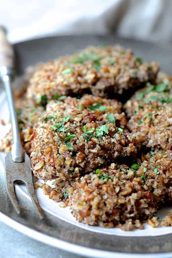Pecan Crusted Turkey Cutlets with Red Onion Marmalade - Close up of turkey cutlets on gray-rimmed platter with serving fork