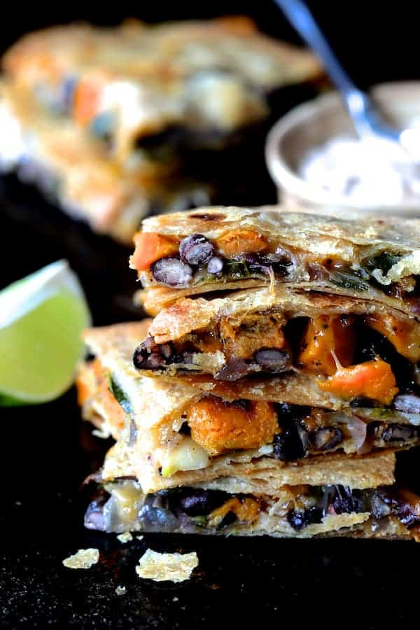 Sheet Pan Quesadillas with Sweet Potatoes, Poblanos and Black Beans with Chipotle Sour Cream - Close-up shot of four stacked quesadilla wedges