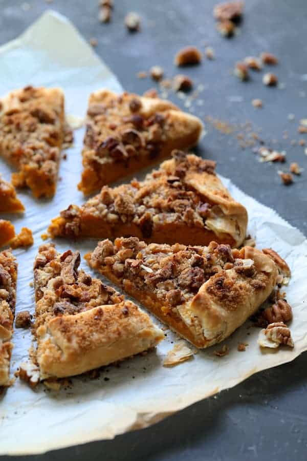 Sweet Potato Galette with Pecan Streusel Topping - Straight-on close-up shot of galette slices on parchment paper