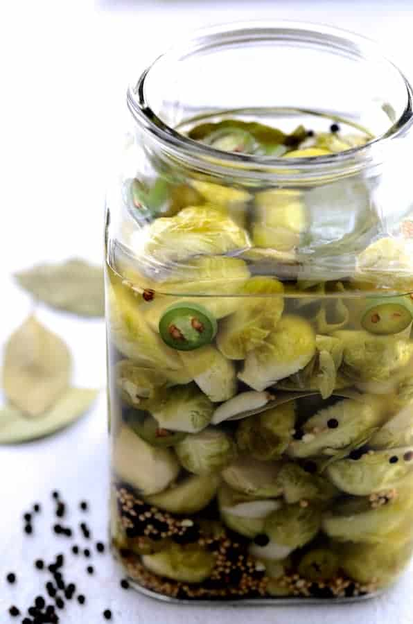 Quick Pickled Brussels Sprouts with Jalapeno in jar without the lid and black peppercorns and bay leaves on the table