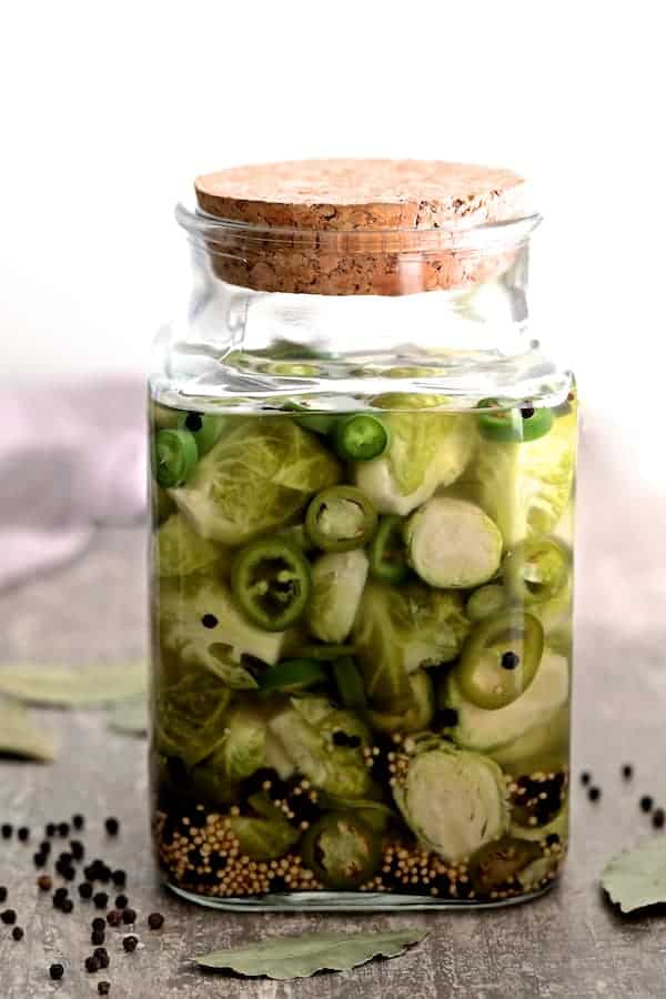 Quick Pickled Brussels Sprouts with Jalapeno in jar with lid on and bay leaves and black peppercorns on the gray table