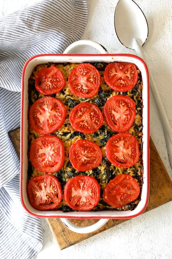 Brown Rice, Cheddar Kale Casserole in white pan on white background with striped towel on wood trivet with white spoon