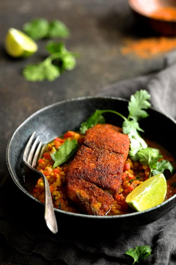 Indian Spiced Sea Bass with Braised Red Lentils in bowl with fork, cilantro sprigs and lime wedges