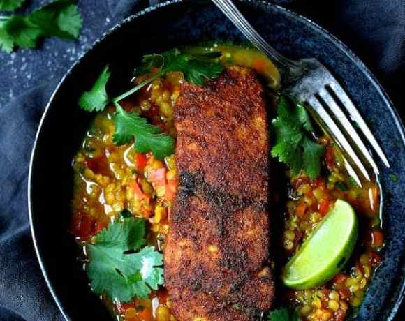 Indian Spiced Sea Bass with Braised Red Lentils overhead close-up shot in bowl with cilantro sprigs and lime wedges