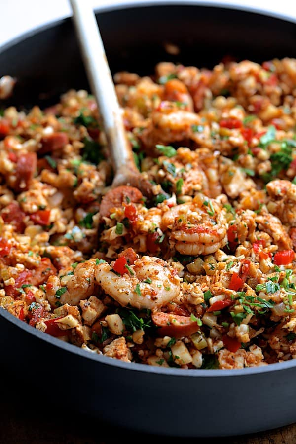 Low Carb Jambalaya with Chicken Shrimp and Sausage being stirred in skillet with wooden spoon