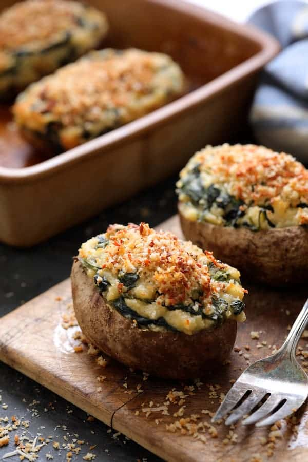 Spinach Parmesan Ranch Twice Baked Potatoes on small wooden cutting board with serving fork in the foreground and clay baking dish in the background