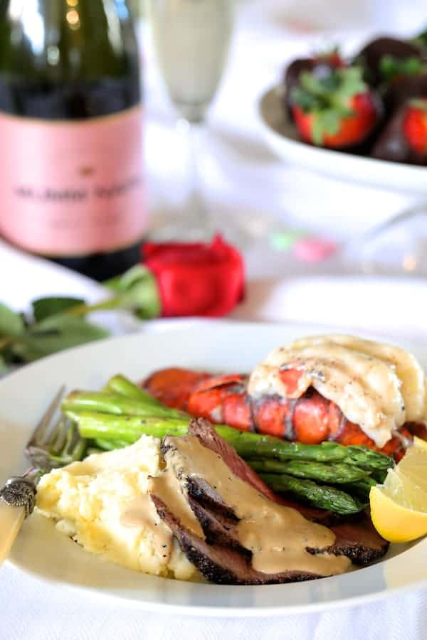 Steak au Poivre and Broiled Lobster Tail with Asparagus on white plate