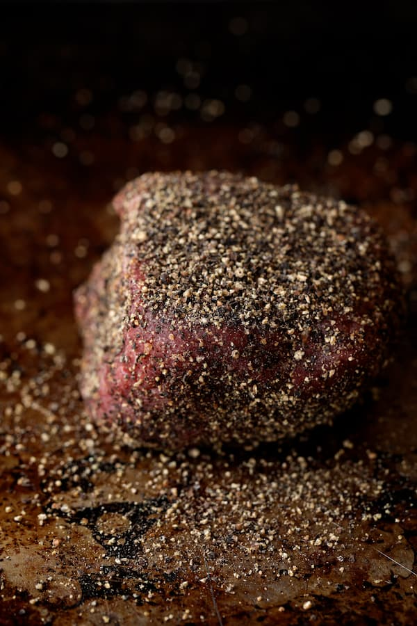 Steak au Poivre and Broiled Lobster Tail - Uncooked steak encrusted with black peppercorns