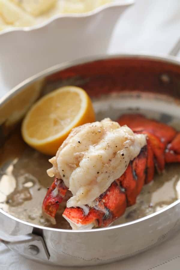 Steak au Poivre and Broiled Lobster Tail - Broiled lobster tail in roasting dish garnished with lemon