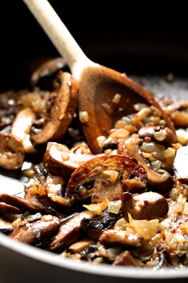 Chicken Meatballs Marsala with Baked Parmesan Polenta - Photo of mushrooms being sauteed in pan with wooden spoon