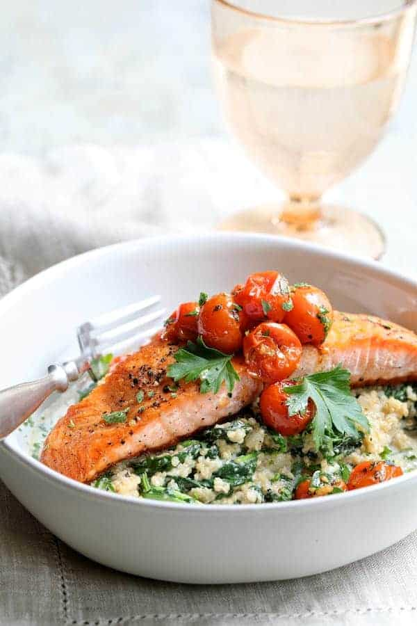 Seared Salmon with Baby Kale Quinotto and Warm Roasted Cherry Tomato Salad - Close-up hero shot of dish in white serving bowl with linen napkin and water goblet