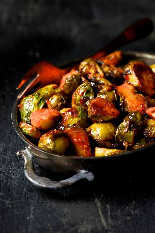 Sriracha Sweet Chili Roasted Brussels Sprouts - side shot in silver oval serving dish with copper fork