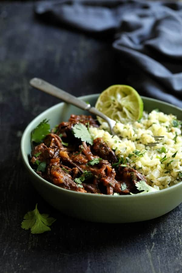 Slow Cooker Beef Short Ribs Barbacoa with Cilantro Lime Cauliflower Rice - Shredded in green serving bowl garnished with cilantro and lime with blue napkin in the background