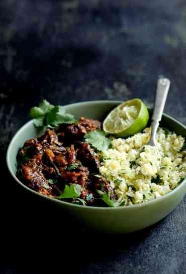 Slow Cooker Beef Short Ribs Barbacoa with Cilantro Lime Cauliflower Rice - Close-up in green serving bowl garnished with cilantro and lime