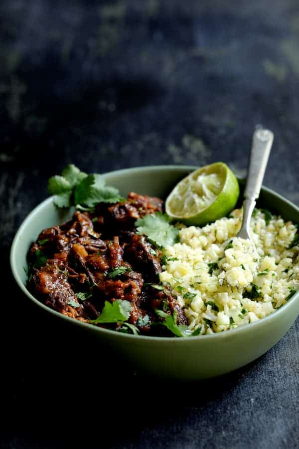 Slow Cooker Beef Short Ribs Barbacoa with Cilantro Lime Cauliflower Rice - Close-up hero shot in green serving bowl garnished with cilantro and lime