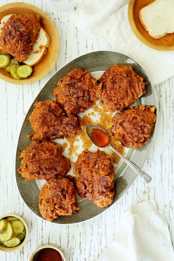 Overhead shot of Nashville Style Hot Fried Chicken on gray-rimmed platter with accompaniments: White bread, pickles and sauce