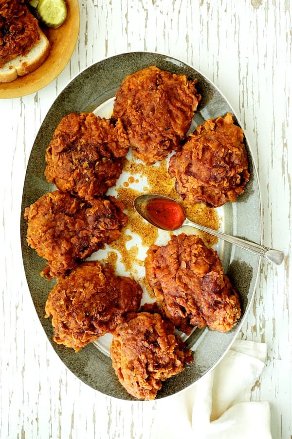 Nashville Style Hot Fried Chicken on gray rimmed platter drizzled with sauce