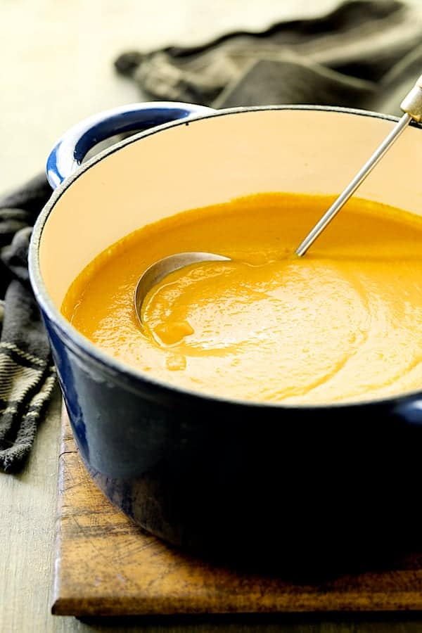 Spicy Indonesian Vegan Carrot Almond Soup - Pureed soup in blue Dutch oven with soup ladle