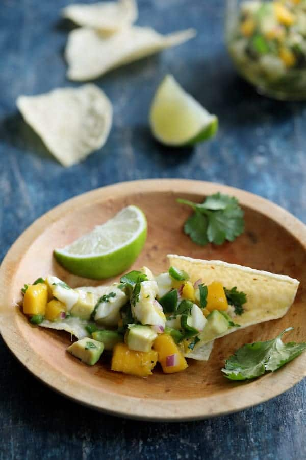 Halibut Ceviche with Mango and Avocado - On tortilla chips in wooden bowl garnished with lime wedge
