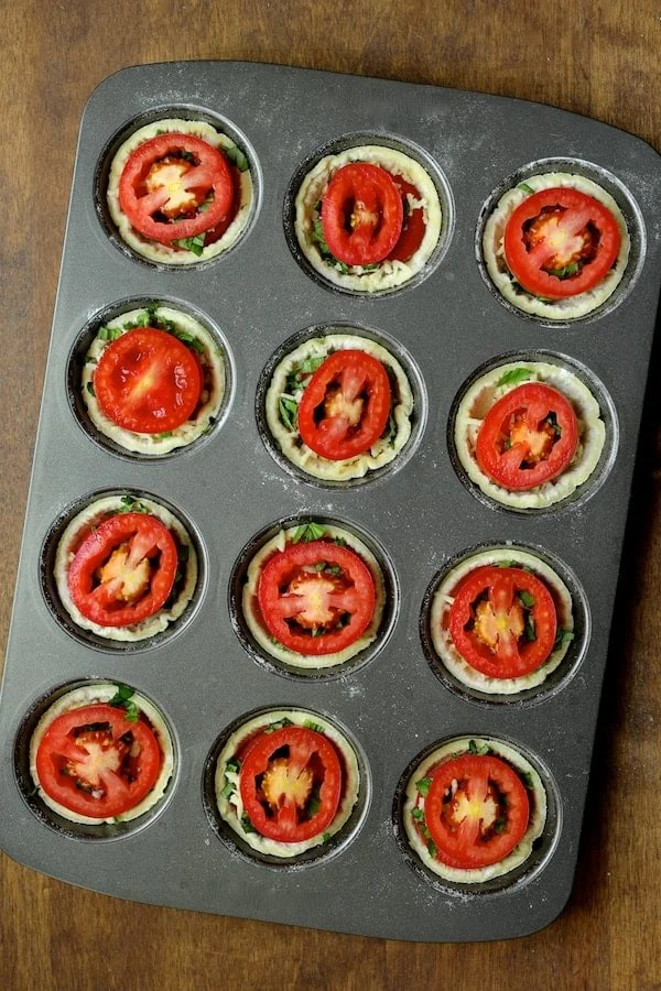 Mini Southern Tomato Pies - Assembly process topped with final tomato slice ready to bake