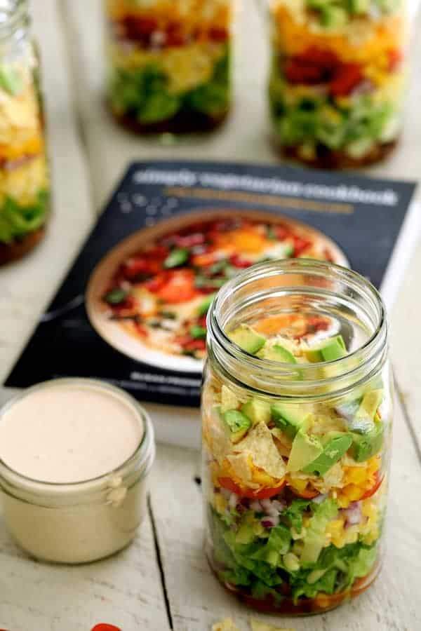 Southwestern Layered Salad - Salad and dressing in foreground with cookbook cover in the background