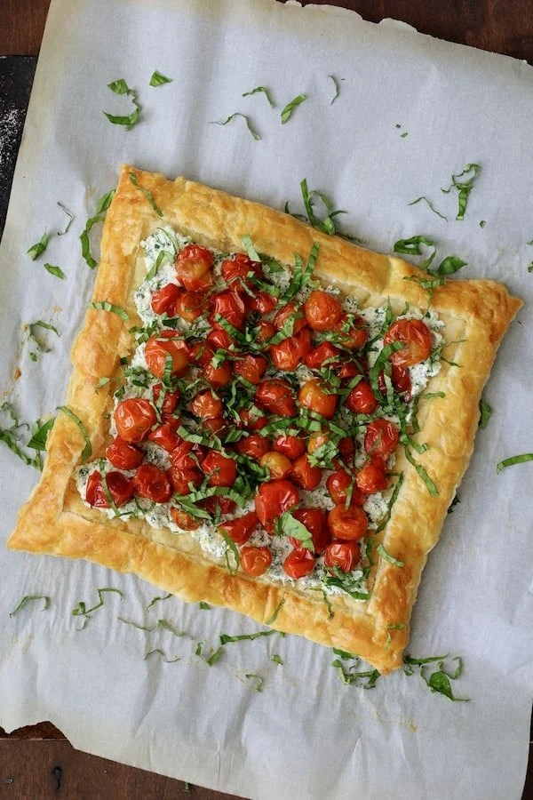 Roasted Cherry Tomato Tart with Herbed Ricotta - Overhead shot of tart with basil sprinkled over the top