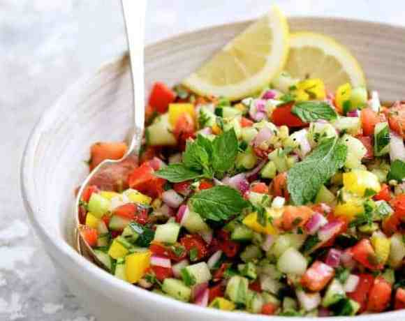 Middle Eastern Chopped Salad - Close-up hero shot of the salad in a white bowl garnished with mint sprigs and lemon slices