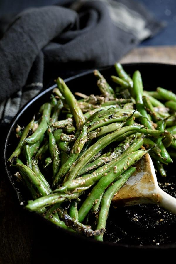 Skillet Charred Green Beans with Goat Cheese Chipotle Butter - Close-up of charred beans with butter in cast iron skillet being stirred with wooden spoon