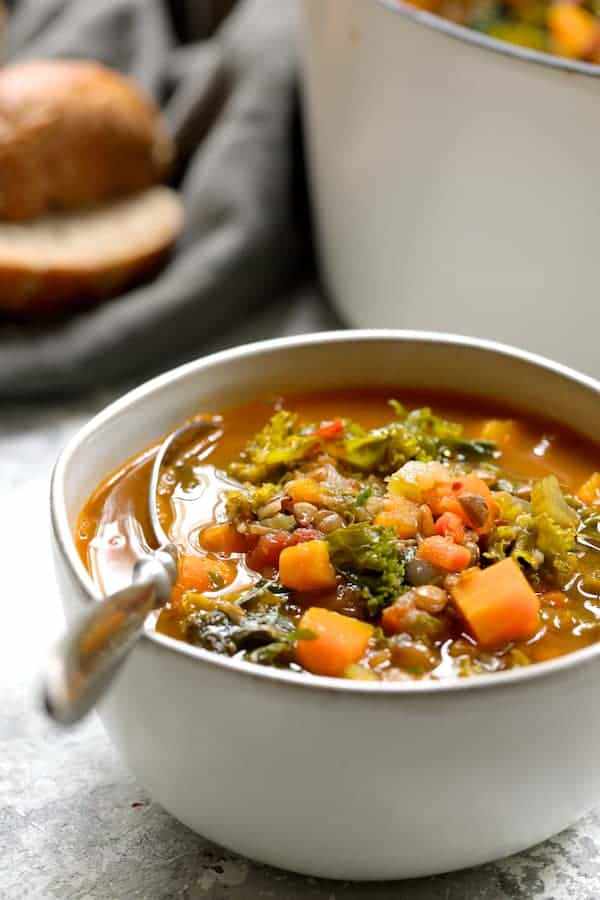 Spicy Kale Butternut Squash and Lentil Soup with Bacon - Side view of soup in white bowl