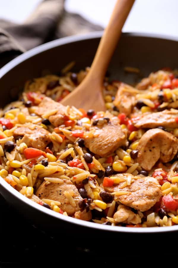 Southwestern Chicken Orzo and Black Bean Skillet - Close-up of finished dish being stirred with wooden spoon