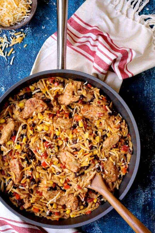 Southwestern Chicken Orzo and Black Bean Skillet - Close-up hero shot with wooden spoon and red and white towel on blue background