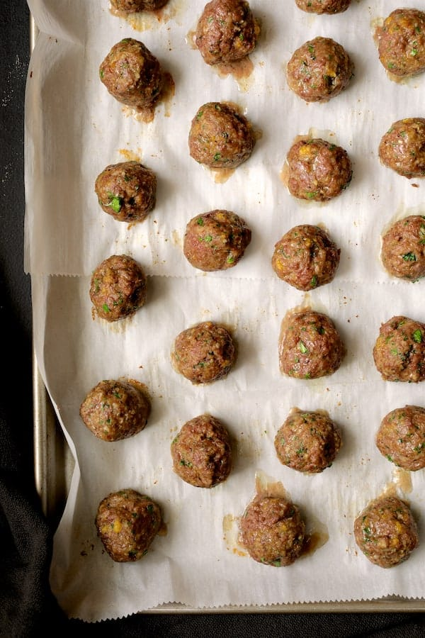 Spiced Meatballs with Tomato Sauce - Overhead shot of baked meatballs on parchment paper