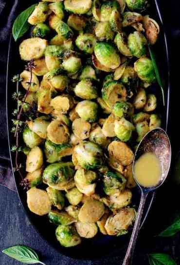 Roasted Brussels Sprouts with Thai Green Curry Butter - Overhead shot of Brussels Sprouts with green curry butter in spoon resting on side of the platter