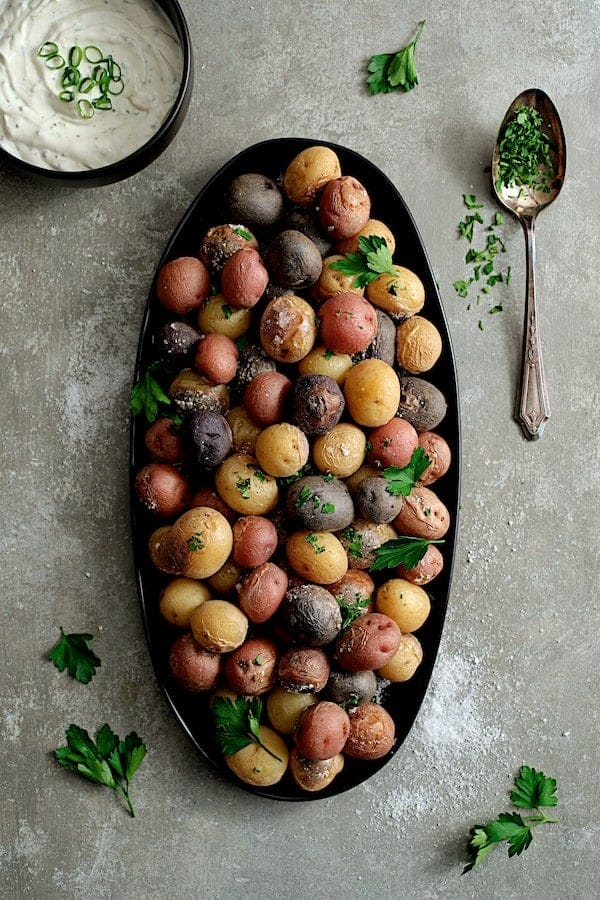 Skillet Salt Roasted Baby Potatoes with Sour Cream Horseradish Sauce - Overhead hero shot of potatoes on black platter, gray background garnished with parsley