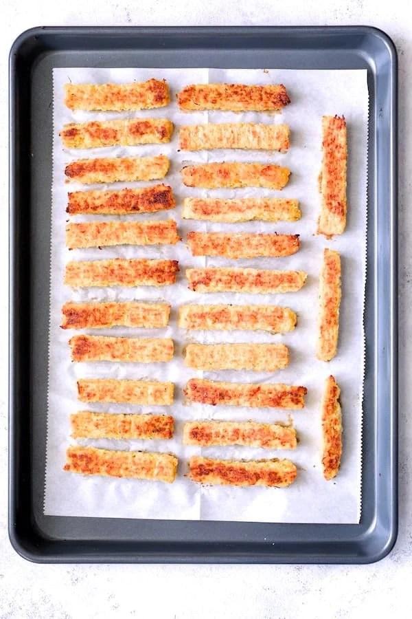 Spaghetti Squash Fries - Baked spaghetti squash fries on parchment paper on baking sheet
