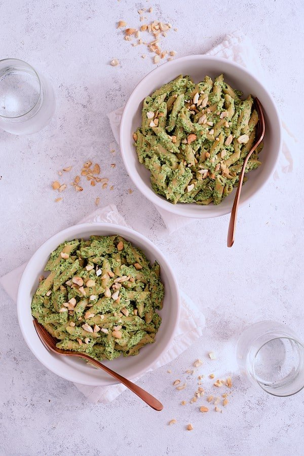 Modern Table Pasta with Creamy Cashew and Spinach Pesto Sauce - Another overhead shot of two bowls of the pasta on white background from slightly farther away