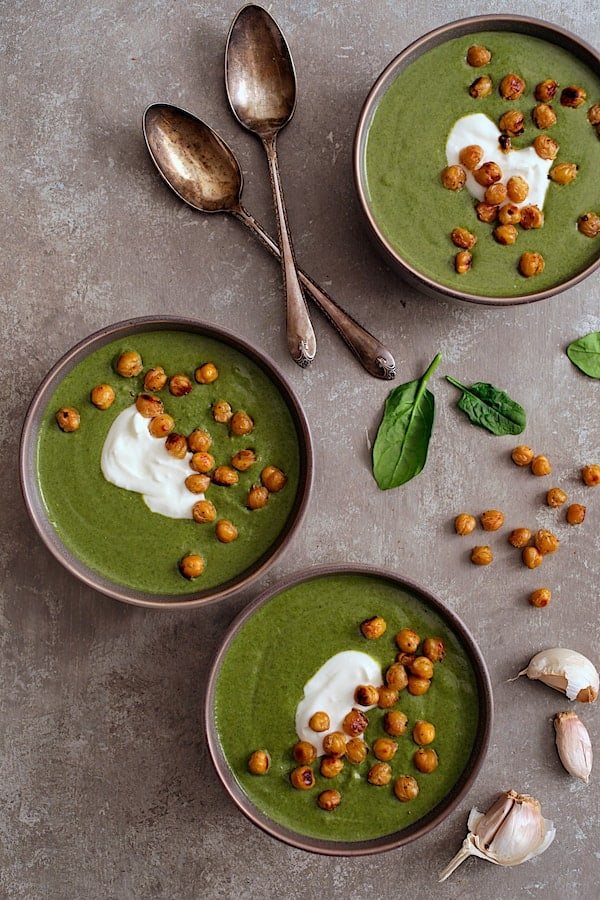 Spinach and Goat Cheese Bisque with Crispy Lemon Chickpeas - Overhead hero shot of soup garnished with yogurt and chickpeas on gray background