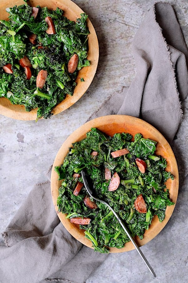 Spicy Sautéed Kale with Andouille Sausage - Overhead shot of dish on two wooden plates on gray background with gray napkin