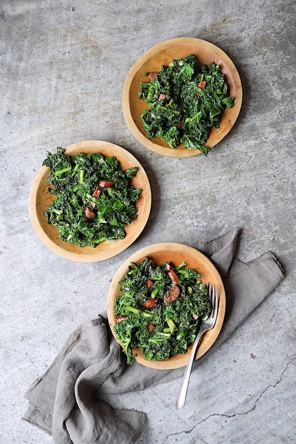 Spicy Sautéed Kale with Andouille Sausage - Overhead shot of dish on three wooden plates
