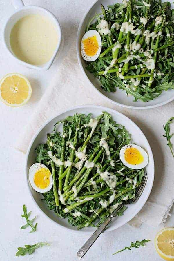 Arugula, Egg and Asparagus Salad with Creamy Lemon Vinaigrette - Overhead hero shot of salad on white plates and white background