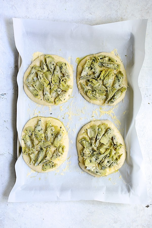 Overhead shot of individual focaccia loaves with artichoke mixture